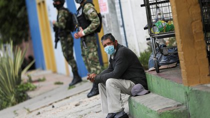 FILE PHOTO: An elderly man wearing a face mask sits on a sidewalk in a street, in one of the neighbourhoods where the mayor's office decreed strict quarantine, amidst an outbreak of the coronavirus disease (COVID-19), in Bogota, Colombia January 5, 2021. REUTERS/Luisa Gonzalez/File Photo