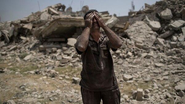 Un hombre lamenta la pérdida de su familia y su hogar en Mosul(AP)