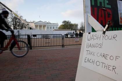 """Un cartel recuerda a la gente que se """"lave las manos """" frente a la Casa Blanca en Washington, EEUU, 26 de marzo de 2020.  REUTERS/Jonathan Ernst"""