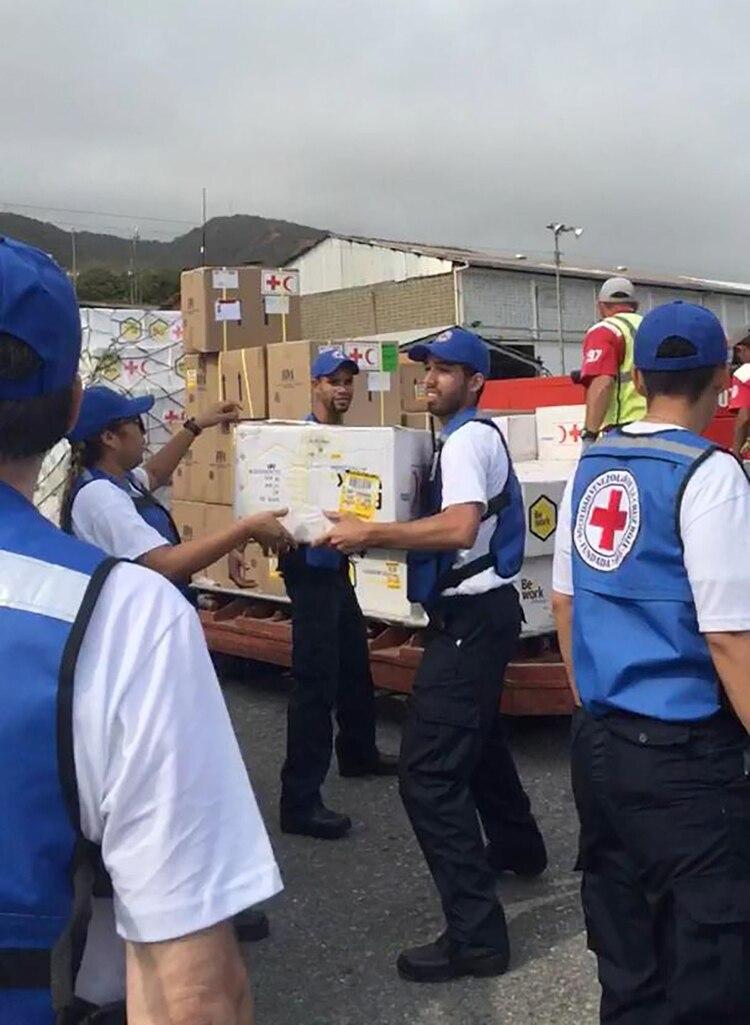Voluntarios de la Cruz Roja empiezan a cargar la ayuda a los camiones (@NTN24ve)
