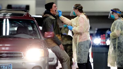 A person receives a throat swab from a healthcare worker at a drive-thru testing site inside the Bismarck Event Center as the coronavirus disease (COVID-19) outbreak continues in Bismarck, North Dakota, U.S., October 26, 2020. REUTERS/Bing Guan