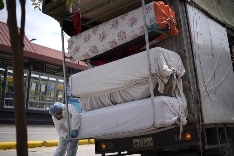 Un trabajador es visto con ataúdes vacíos enviados desde Quito al Instituto de Seguridad Social de Ecuador, mientras la enfermedad coronavirus (COVID-19) abruma a las autoridades sanitarias, en Guayaquil