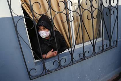 Una inmigrante peruana con barbijo mira por la ventana en Santiago, Chile (REUTERS/Ivan Alvarado)