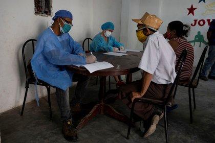 Dos médicos atienden personas, el 25 de septiembre de 2020, durante una jornada de pruebas rápidas de la covid-19, en Caracas (Venezuela). EFE/Rayner Peña R/Archivo