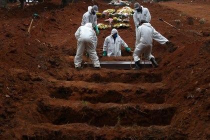 Sepultureros con trajes protectores entierran el ataúd de José Soares, de 48 años, quien murió a causa de COVID-19 (Reuters)