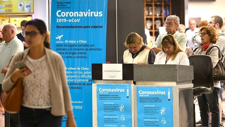 Los carteles celestes en el aeropuerto de Ezeiza para informar del Coronavirus (Foto: Gustavo Gavotti)