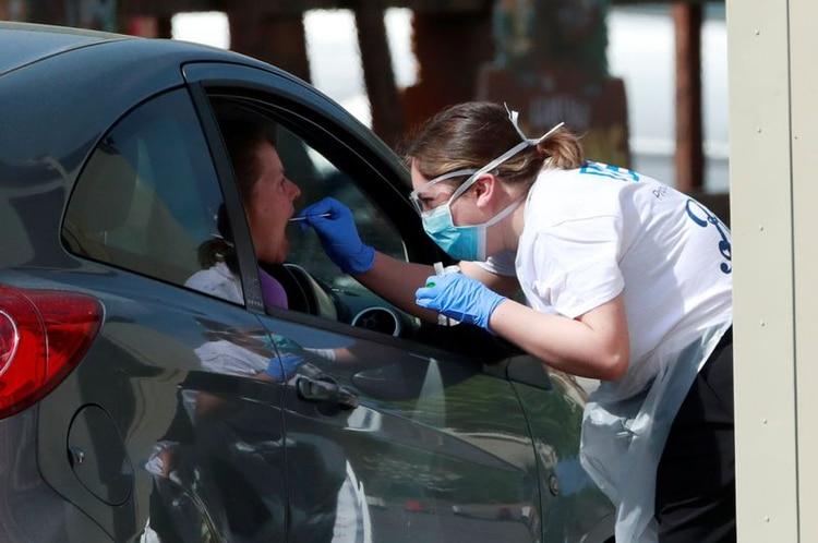 Una mujer es examinada en un centro de pruebas de coronavirus en el aparcamiento del Chessington World of Adventures, Chessington, Reino Unido, 15 de abril de 2020. REUTERS/Andrew Couldridge