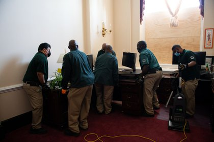 Workers clean an office at the U.S. Capitol building in Washington, D.C., U.S., on Thursday, Jan. 7, 2021. Joe Biden was formally recognized by Congress as the next U.S. president early Thursday, ending two months of failed challenges by his predecessor, Donald Trump, that exploded into violence at the U.S. Capitol as lawmakers met to ratify the election result.