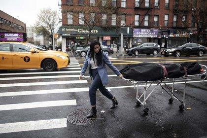 Alisha Narvaez, directora de un servicio de cremación en Nueva York,  traslada el cuerpo de una víctima de covid-19 por una calle de Harlem. (24 de abril)