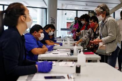 Foto referencial de archivo de trabajadores de salud revisando documentos a pasajeros en el aeropuerto de Santiago, Chile Abril, 2020. REUTERS/Lucas Alvarado