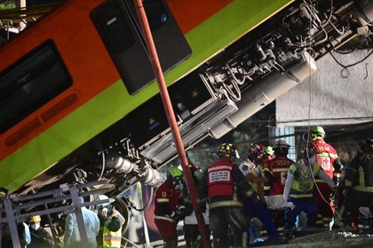 Rescue workers remove a body from a train carriage after an elevated metro line collapsed in Mexico City on May 4, 2021. (Photo by PEDRO PARDO / AFP)