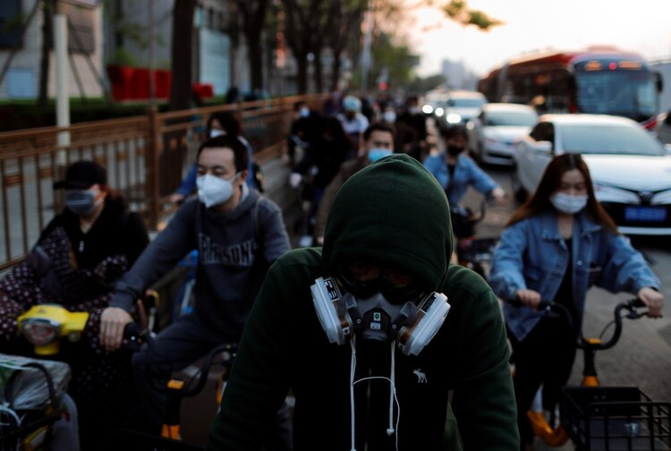 Gente con máscaras a la salida del trabajo en el distrito financiero de Beijing, China REUTERS/Thomas Peter