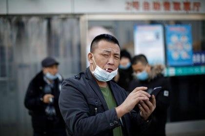 Un hombre chino fuma pese a tener el barbijo puesto y en plena pandemia -  REUTERS/Carlos Garcia Rawlins
