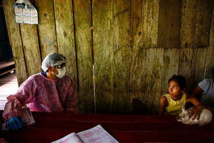 En el marco de la pandemia del nuevo coronavirus, un trabajador del sistema de salud municipal de Brasil habla con una familia durante las visitas a domicilio que se realizaron a orillas del lago Mirini, en la región amazónica de Brasil (Diego Baravelli /MSF)