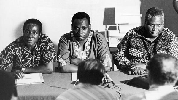 Rober Mugabe (izquierda) asiste a una reunión en Dar Es Salaam, Tanzania como líder de las fuerzas de combate rodesianas a principios de la década del sesenta. A su lado, Georges Silundika, secretario de información y vicedirector del Congreso Nacional Africano, y Joshua Nkomo, líder del partido Zimbabwean African People Union