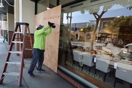 Un hombre coloca una plancha de madera en un comercio en Los Ángeles. Foto: REUTERS/Lucy Nicholson