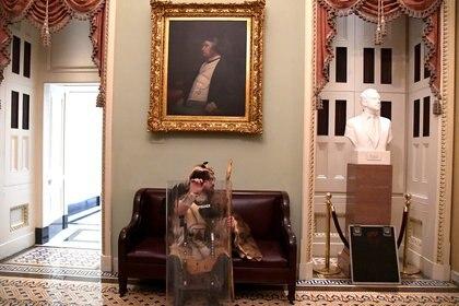 Un simpatizante de Trump descansa en un mueble en medio del asedio (Reuters)