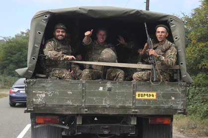 Soldados de origen étnico armenio reaccionan mientras viajan en la parte trasera de un camión en la región escindida de Nagorno-Karabaj el 29 de septiembre de 2020 (Vahram Baghdasaryan/Photolure via REUTERS)