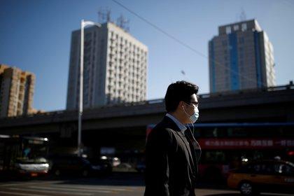 Un hombre con barbijo camina en Beijing durante la pandemia del coronavirus (REUTERS/Carlos Garcia Rawlins)
