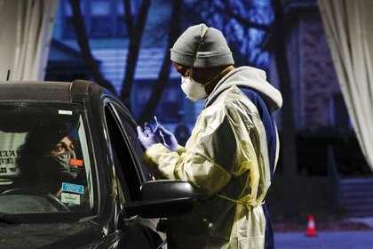Un agente sanitario se dispone a tomar una muestra de una paciente en un puesto móvil de pruebas de COVID-19 en Milwaukee, en el estado de Wisconsin (REUTERS/Bing Guan)