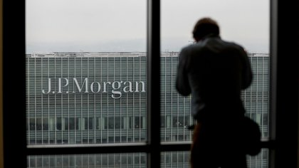 A man looks out of a window to the offices of JPMorgan Chase & Co. in the Canary Wharf business and shopping district in London.