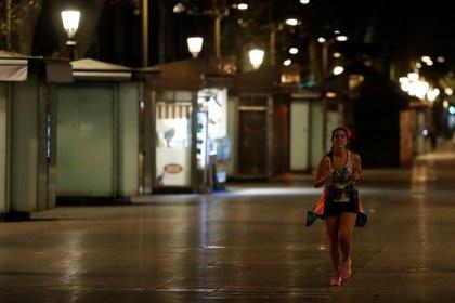 Una mujer corre en Las Ramblas durante el primer día del toque de queda nocturno, parte de un esfuerzo por controlar el brote de la enfermedad del coronavirus (COVID-19), en Barcelona, España. 25 de octubre de 2020. REUTERS/Nacho Doce
