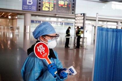Un empleado con ropa de protección preparado para tomar la temperatura de los visitantes en el aeropuerto de Pekín.  Mar 4, 2020. REUTERS/Thomas Peter