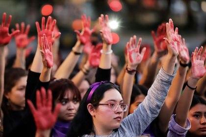 Mujeres levantan sus manos pintadas de rojo en una protesta en contra de la violencia de género y el feminicidio, en Puebla, México. (Foto: REUTERS/Imelda Medina)
