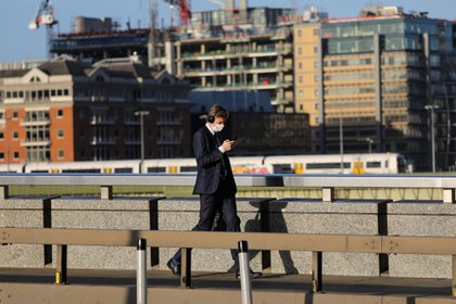 A commuter, wearing a protective face mask, looks at his mobile phone as he crosses London Bridge in London, U.K., on Thursday, Oct. 15, 2020. London is on course for an imminent tightening of coronavirus restrictions, as cases continue to rise in Britain and its response fragments. Photographer: Simon Dawson/Bloomberg