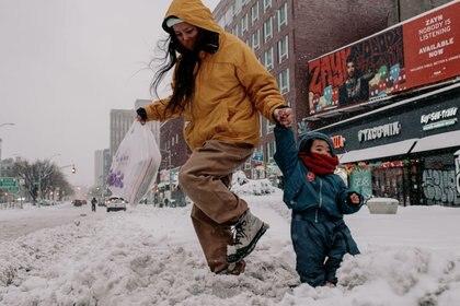 Una mujer y un niño cruzan una calle llena de nieve en Manhattan (Scott Heins/Getty Images/AFP)