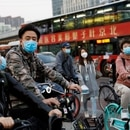 People wearing protective face masks ride bicycles on a street, following an outbreak of the coronavirus disease (COVID-19), in Beijing, China April 7, 2020. REUTERS/Carlos Garcia Rawlins