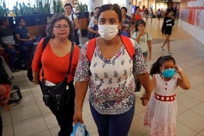 Varias personas con mascarillas caminan por el Aeropuerto Internacional Jorge Chávez en Lima, Perú. 6 marzo 2020. REUTERS/Sebastián Castañeda