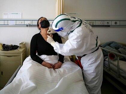 Un paciente con COVID-19 recibe tratamiento con acupuntura en un hospital de la Cruz Roja en Wuhan, China (STR / AFP)