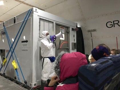 Un funcionario de salud estadounidense da indicaciones a los pasajeros evacuados (Reuters)