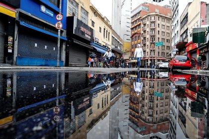 Fotografía de locales comerciales cerrados, en la calle 25 de marzo, el mayor centro del comercio popular de San Pablo (EFE/ Sebastião Moreira)