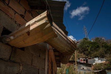 En la imagen se observa un sistema artesanal de canales para recoger agua de lluvia en el techo de una casa (EFE/ Miguel Gutiérrez)