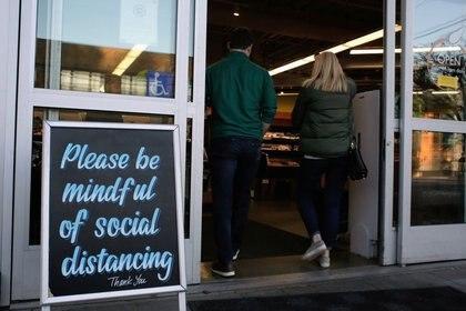Los compradores entran en una tienda de comestibles que en su entrada tiene un cartel que solicita el distanciamiento social, tras los informes de casos de enfermedad coronavirus (COVID-19) en la zona, en Seattle, Washington, EEUU (17 de marzo de 2020/ Reuters/ David Ryder)