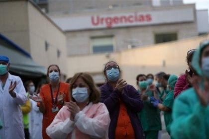 Personal médico saluda ante los aplausos de los vecinos en Madrid (Reuters)
