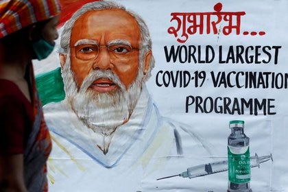 FOTO DE ARCHIVO: Una mujer pasa junto a un cuadro del primer ministro indio Narendra Modi un día antes de la inauguración de la campaña de vacunación COVID-19 en una calle de Mumbai, India, el 15 de enero de 2021. REUTERS/Francis Mascarenhas/File Photo