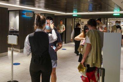 Empleados miden la temperatura de pasajeros al entrar a un restaurante en el crucero MSC Grandiosa en Civitavecchia, cerca de Roma, el 31 de marzo de 2021 (Foto AP/Andrew Medichini)