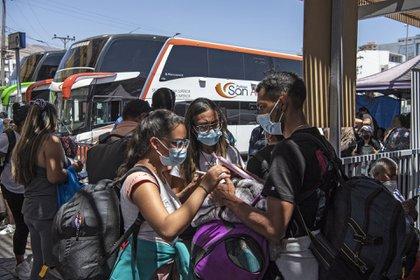 Los migrantes venezolanos Reinaldo (R), 26, Anyier (C), 40, y su hija Danyierly, 14, se preparan para abordar un autobús hacia Santiago, en Iquique, Chile, el 19 de febrero de 2021, luego de cruzar la frontera con Bolivia (MARTIN BERNETTI / AFP)