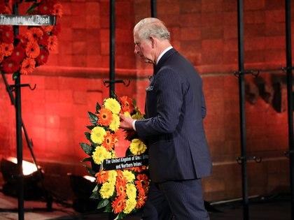 """El príncipe Carlos de Gales, hijo de la reina Isabel II del Reino Unido, lleva una corona de flores al escenario: """"El tiempo de prácticamente una vida ha pasado desde que el horror del holocausto tuvo lugar en el continente europeo, y lamentablemente aquellos que fueron testigos de ello son cada vez menos. Debemos, en consecuencia, comprometernos a asegurarnos que sus historias sobrevivan, que sean conocidas y entendidas por cada generación que les siga"""", expresó.  Foto: Abir Sultan/REUTERS"""