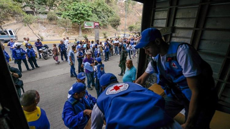 Miembros de la Cruz Roja distribuyen la ayuda humanitaria (AFP)