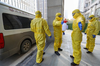 Personal de una funeraria, en trajes de protección para transferir a un cuerpo desde un hospital en Wuhan (Reuters)