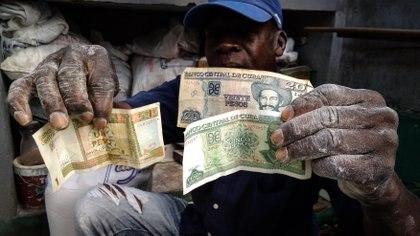Un trabajador cubano sostiene un peso CUC, atado al dólar, y su equivalente en 25 pesos CUP (AFP)
