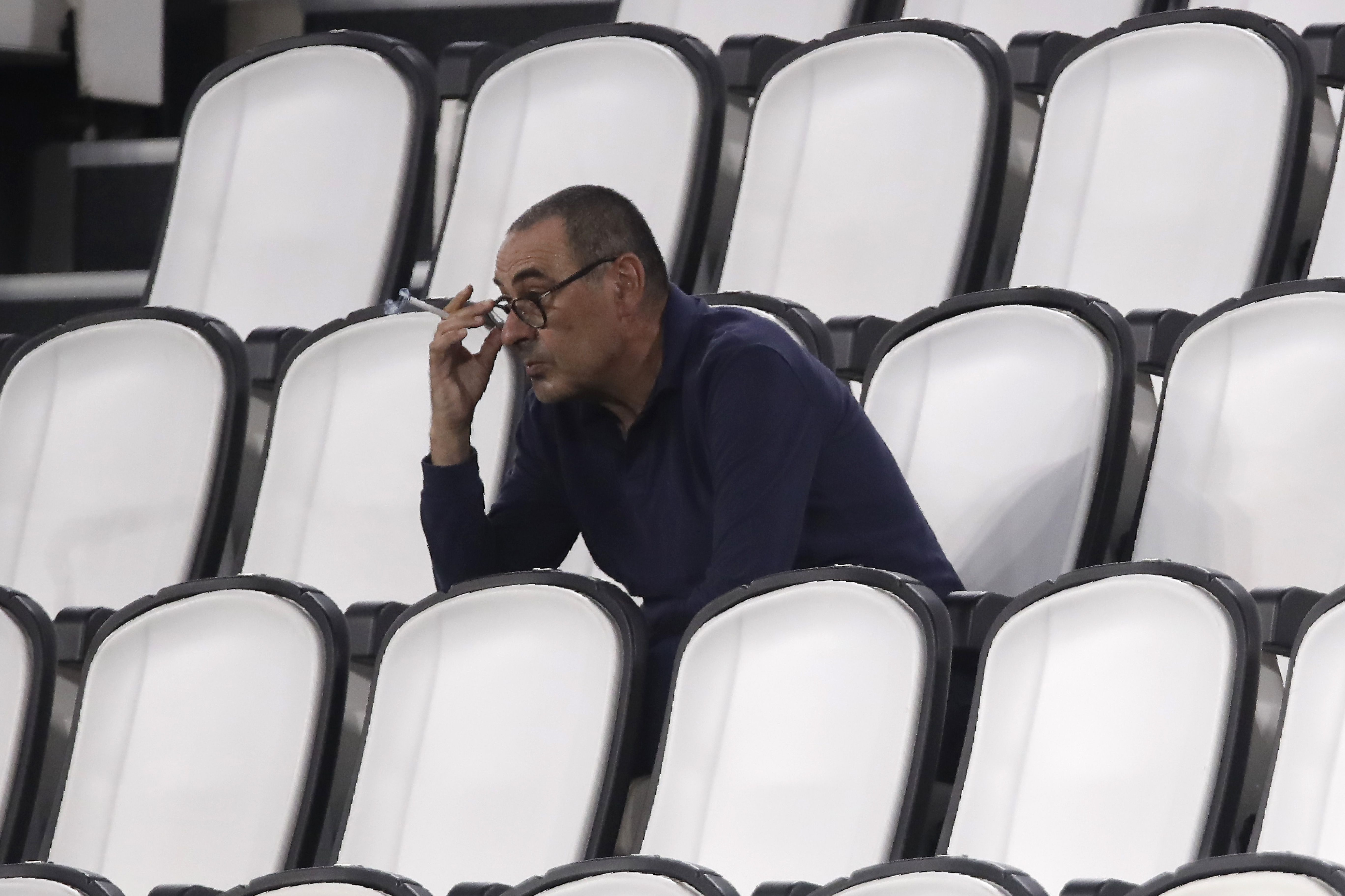 FILE - In this Saturday, Aug. 1, 2020 filer, Juventus' head coach Maurizio Sarri smokes during a Serie A soccer match between Juventus and Roma, at the Allianz stadium in Turin, Italy. Cristiano Ronaldo scored twice but could not prevent Juventus from going out of the Champions League despite a 2-1 victory over Lyon in its rearranged second-leg match Friday. The French team progressed to the quarterfinals on away goals after a 2-2 draw on aggregate. (AP Photo/Luca Bruno, File)