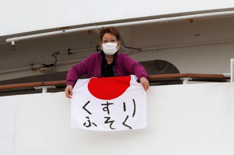 Una mujer sostiene una bandera japonesa que dice