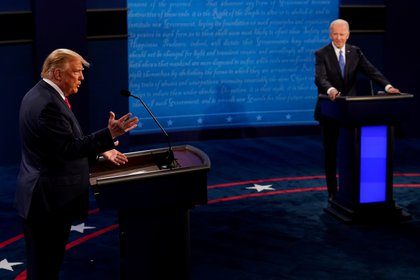 U.S. President Donald Trump answers a question as Democratic presidential candidate former Vice President Joe Biden listens during the second and final presidential debate at the Curb Event Center at Belmont University in Nashville, Tennessee, U.S., October 22, 2020. Morry Gash/Pool via REUTERS