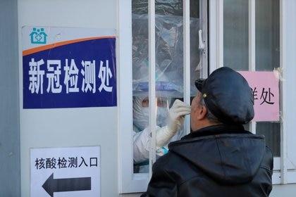 Un trabajador médico con traje protector toma un hisopo de un hombre para realizar una prueba de ácido nucleico en un hospital en Shenyang, China, 31 diciembre 2020.<br/>cnsphoto vía REUTERS