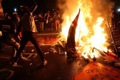 Manifestantes queman una bandera de los Estados Unidos durante las protestas del domingo a la noche en Washington.  REUTERS/Jonathan Ernst